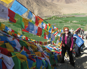 Inveterate world traveler Falvey in Tibet, with prayer flags at Yongbulakang