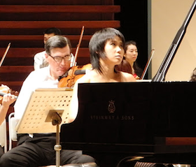 Yuja Wang rehearsing for the final tour concert; violinist/composer Mark Volkert is seen behind her