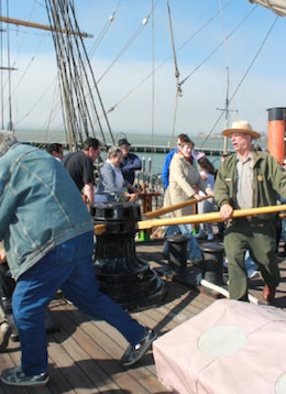 "Ranger Peter Kasin (right) leads chantey workshoppers around the capstan of the Balclutha, to the tune of ""Paddy Lay Back"".   --- Photo by Jeff Kaliss"