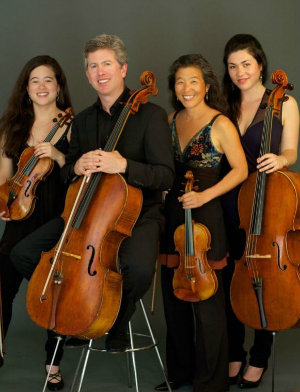 """(Almost) All in the Family"": husband and wife cellist Peter Wyrick and violinist Amy Hiraga have their cellist daughter Mariko Hiraga Wyrick (right) in the orchestra with them on the tour; violinist daughter Mayumi Hiraga Wyrick (left) would make it a quartet-within-orchestra"