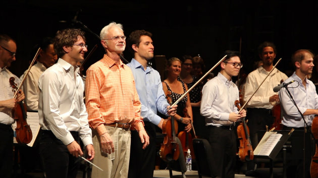Teddy Abrams and John Adams taking a bow in front of the Dover String Quartet and the Britt Orchestra (Photo courtesy of musicmakesacity.com)
