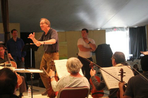 "Festival co-founder and conductor Allan Pollack leads the Festival Orchestra through a rehearsal of ""The Barber of Seville"", with opera director and baritone Eugene Brancoveanu (in white t-shirt). (Photo by Jeff Kaliss)"
